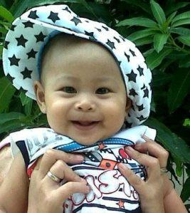 bayi tersenyum ceria salah satu fungsi dari pijatan yang ibu berikan